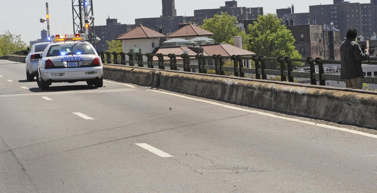 Tire skid marks cross the highway where a van plunged over both the concrete and iron railing, Sunday, April 29, 2012, in New York. Authorities say the out-of-control van plunged off a roadway near the Bronx Zoo, killing seven people, including three children. (AP Photo/ Louis Lanzano)