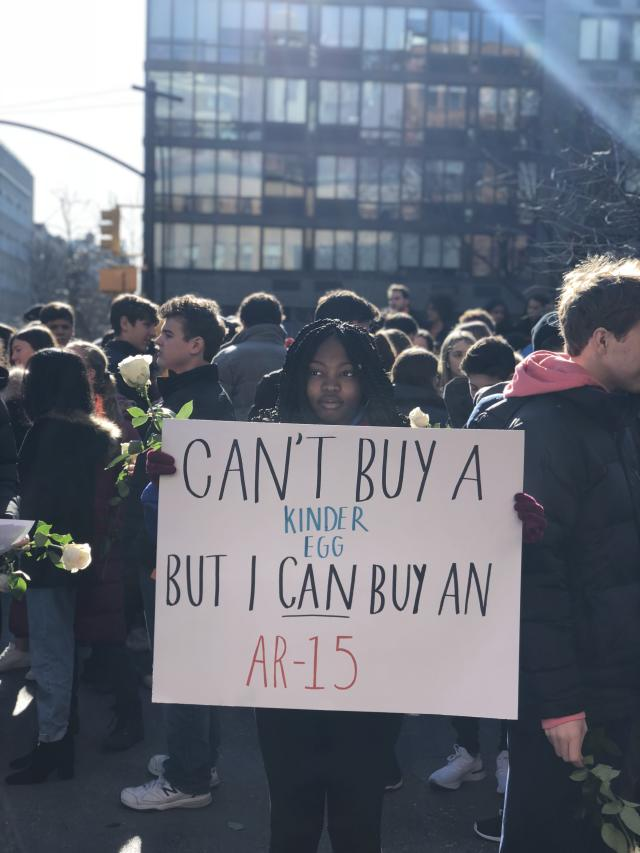 A student from Grace Church School in New York City holds a sign made for the day's protests. (Photo: Alexandra Mondalek)