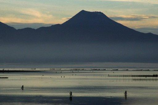 Fishermen are seen near the Mount Bulusan volcano on the main island of Luzon