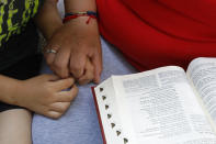 Eugenia Rodriguez holds the hand of her youngest son, Aaron, 6, while reading from the Bible in her house, Friday, July 2, 2021, in Chicago's Little Village neighborhood. Rodriguez hasn't been eligible for insurance coverage after overstaying a visitor visa from Mexico. She used to wake up every two or three hours at night to check on her mother. Since getting health insurance through the Illinois program, her mother has all the medications she needs. (AP Photo/Shafkat Anowar)