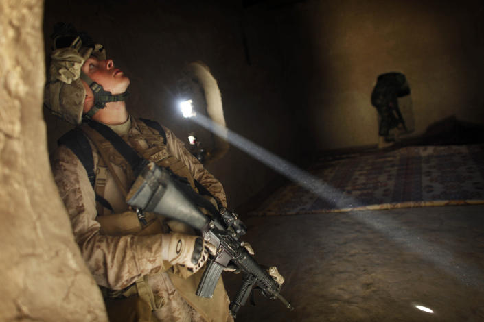 """FILE - In this Dec. 23, 2009 file photo, United States Marine LCpl. Franklin Romans of Michigan, from the 2nd Battalion 2nd Marines """"Warlords"""" searches a house during an operation in the Garmsir district of the volatile Helmand province, southern Afghanistan. After 20 years America is ending its """"forever"""" war in Afghanistan. There's conflicting views even among U. S. military minds as to whether the time is right. For others there is another lingering question: Was it worth it? (AP Photo/Kevin Frayer, File)"""