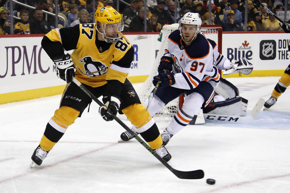 Pittsburgh Penguins' Sidney Crosby (87) gets off a backhand pass with Edmonton Oilers' Connor McDavid (97) defending during the second period of an NHL hockey game in Pittsburgh, Saturday, Nov. 2, 2019. (AP Photo/Gene J. Puskar)