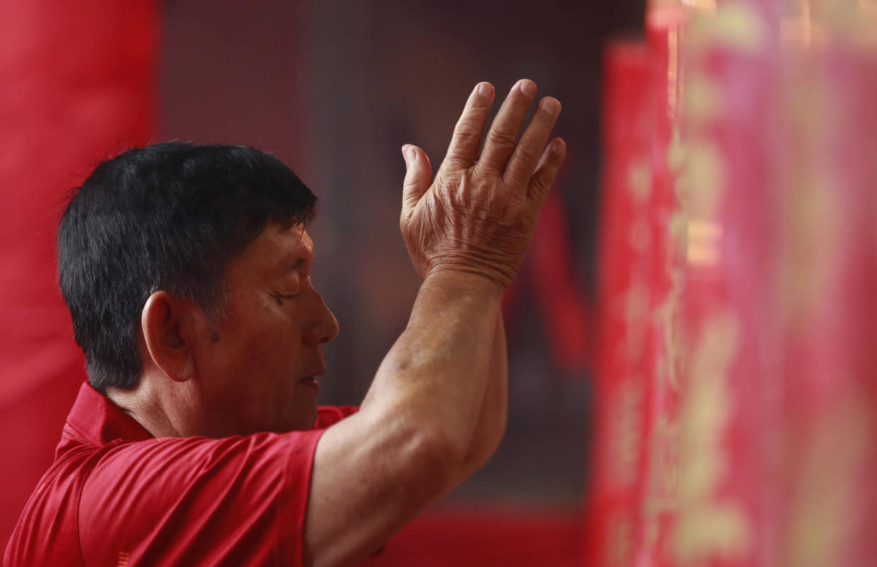 An ethnic Chinese man prays during celebrations of the Lunar New Year at the Dharma Bakti Temple in Jakarta, Indonesia, Saturday, Jan. 28, 2017. Ethnic Chinese in the world's most populous Muslim country are celebrating the Year of the Rooster. (AP Photo/Achmad Ibrahim)