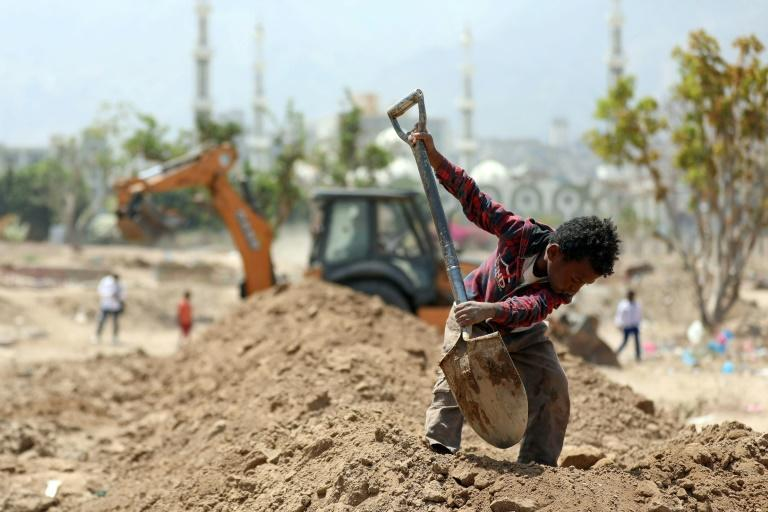 A Yemeni worker digs graves as a bulldozer operates at a plot for Covid-19 victims at a cemetery in Yemen's third city of Taez