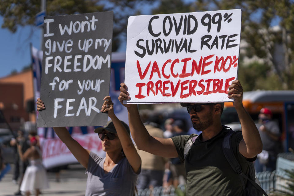FILE - In this Sept. 18, 2021, file photo, protesters opposing COVID-19 vaccine mandates hold a rally in front of City Hall in downtown Los Angeles. COVID-19 deaths in the U.S. have climbed to an average of more than 1,900 a day for the first time since early March, with experts saying the virus is preying largely on a select group: 71 million unvaccinated Americans. (AP Photo/Damian Dovarganes, File)