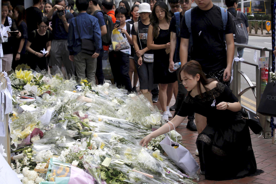 Mourners stop by a makeshift memorial, to lay flowers and pray for a man who fell to his death Saturday after hanging a protest banner against an extradition bill in Hong Kong Sunday, June 16, 2019. Tens of thousands of Hong Kong residents, mostly in black, have jammed the city's streets Sunday to protest the government's handling of a proposed extradition bill. (AP Photo/Kin Cheung)