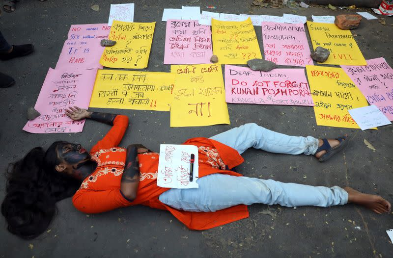 A student lies on the ground as she plays dead during a protest against the alleged rape and murder of a 27-year-old woman, in Kolkata