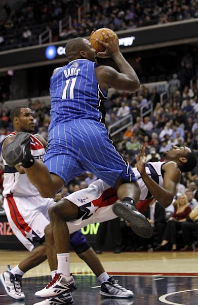 "FILE - In this Feb. 29, 2012, file photo, Orlando Magic power forward Glen Davis (11) charges into Washington Wizards point guard John Wall (2) during the first half of an NBA basketball game in Washington. The NBA will penalize flopping this season, fining players for repeated violations of an act a league vice president says has ""no place in our game."" The league said Wednesday, Oct. 3, 2012, that flopping will be defined as ""any physical act that appears to have been intended to cause the referees to call a foul on another player."" (AP Photo/Haraz N. Ghanbari, File)"