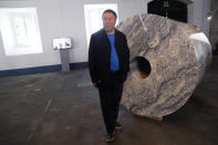 """Dissident Chinese artist Ai Weiwei poses by one of his latest works, a giant toilet paper roll in marble, during a press preview of his new exhibition """"Rapture"""" in Lisbon, Thursday, June 3, 2021. The world-renowned artist is putting on the biggest show of his career, and he is doing it in a place he's fallen in love with: Portugal. (AP Photo/Armando Franca)"""