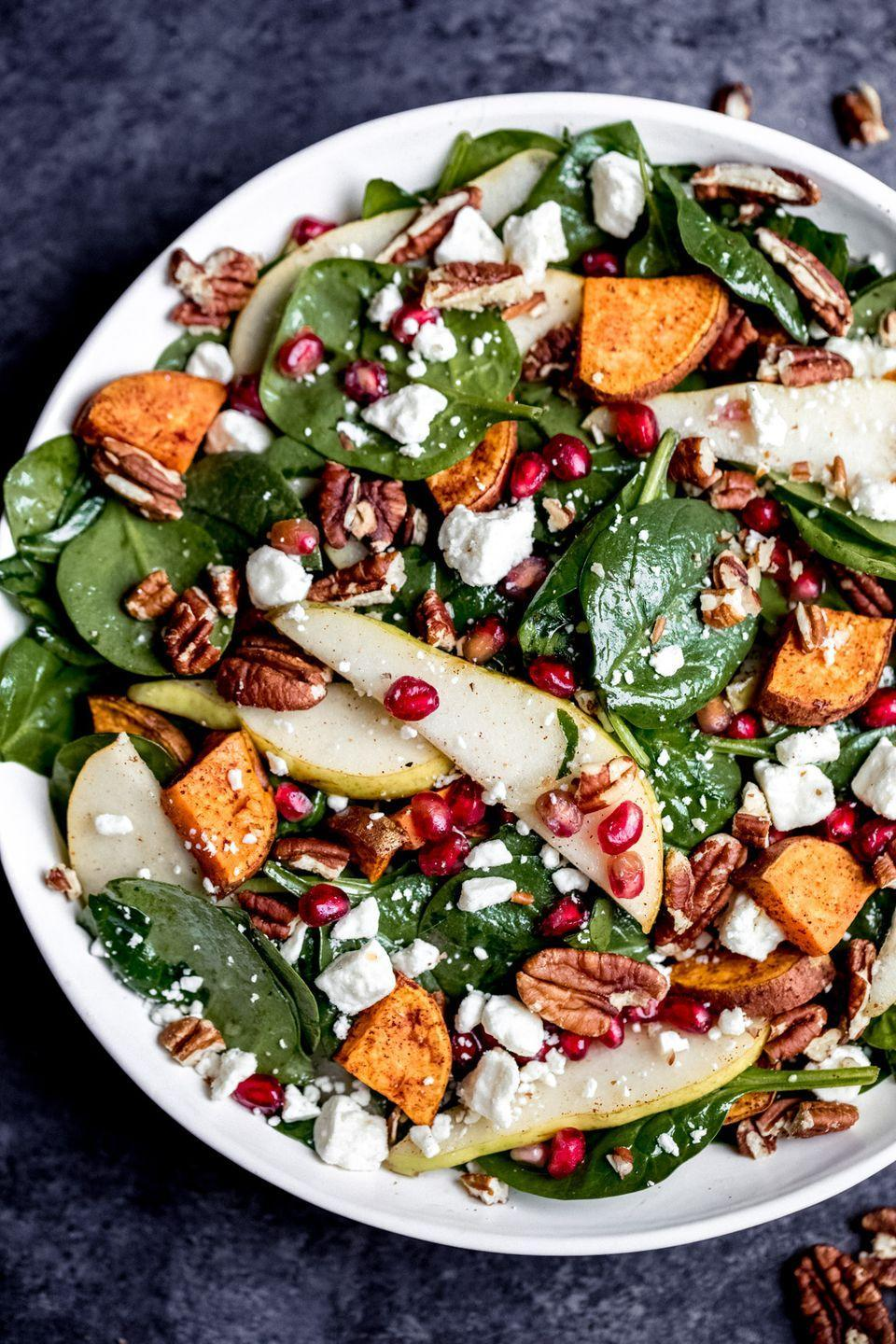 """<p>This salad will be a stunning feature on your New Year's Eve dinner table, especially with the seasonal flavors from the sweet potato and pecans mixed together with the sweet pomegranates and pears.</p><p><strong>Get the recipe at <a href=""""https://www.ambitiouskitchen.com/sweet-potato-pear-pomegranate-spinach-salad/"""" rel=""""nofollow noopener"""" target=""""_blank"""" data-ylk=""""slk:Ambitious Kitchen"""" class=""""link rapid-noclick-resp"""">Ambitious Kitchen</a>.</strong> </p>"""
