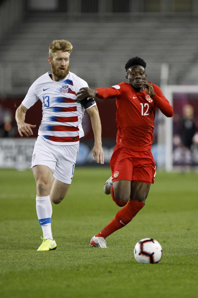 U.S. defender Tim Ream (13) and Canada midfielder Alphonso Davies (12) chase the ball during the first half of a CONCACAF Nations League soccer match Tuesday, Oct. 15, 2019, in Toronto. (Cole Burston/The Canadian Press via AP
