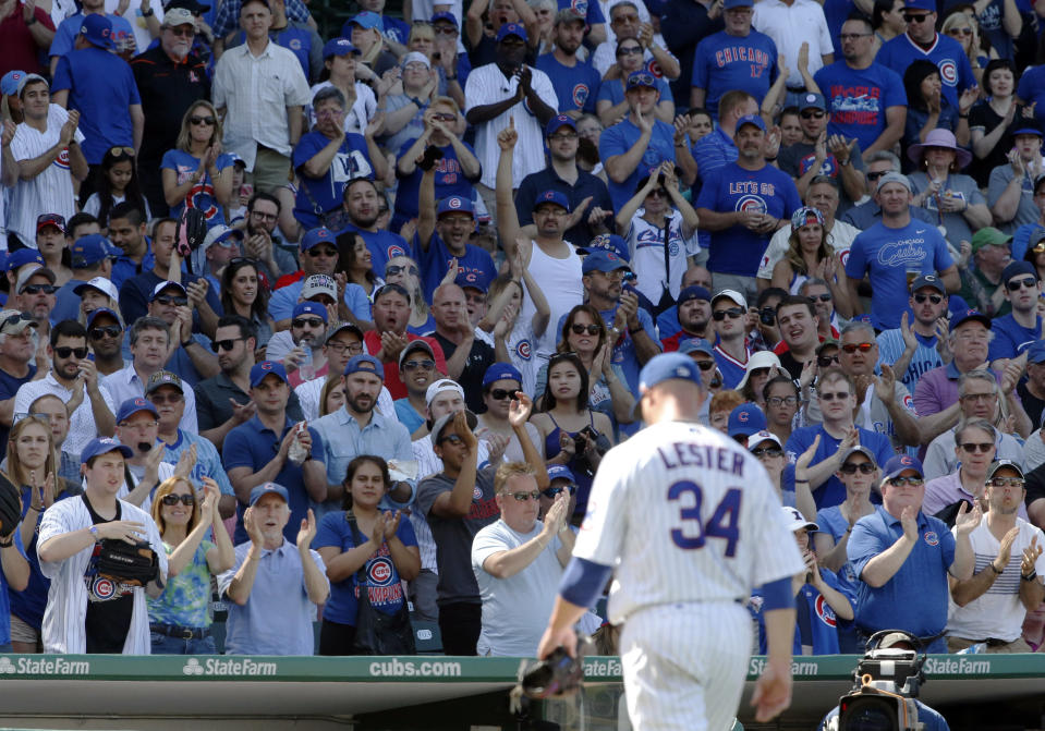 Jon Lester walks off with fans cheering in the stands.