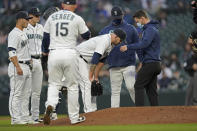 Seattle Mariners starting pitcher James Paxton, third from right, talks with manger Scott Servais, second from right, and a trainer after he experienced an injury, during the second inning of the team's baseball game against the Chicago White Sox on Tuesday, April 6, 2021, in Seattle. Paxton left the game. (AP Photo/Ted S. Warren)
