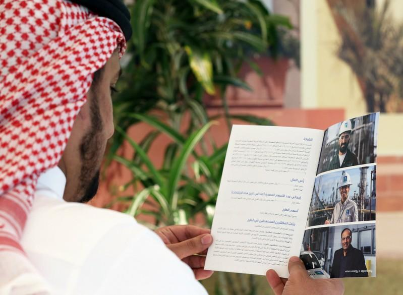 A Saudi man reads the prospectus of Aramco IPO, in Riyadh