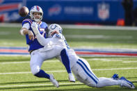 Buffalo Bills quarterback Josh Allen (17) throws a pass as he is hit by Indianapolis Colts' DeForest Buckner (99) during the second half of an NFL wild-card playoff football game Saturday, Jan. 9, 2021, in Orchard Park, N.Y. (AP Photo/Adrian Kraus)