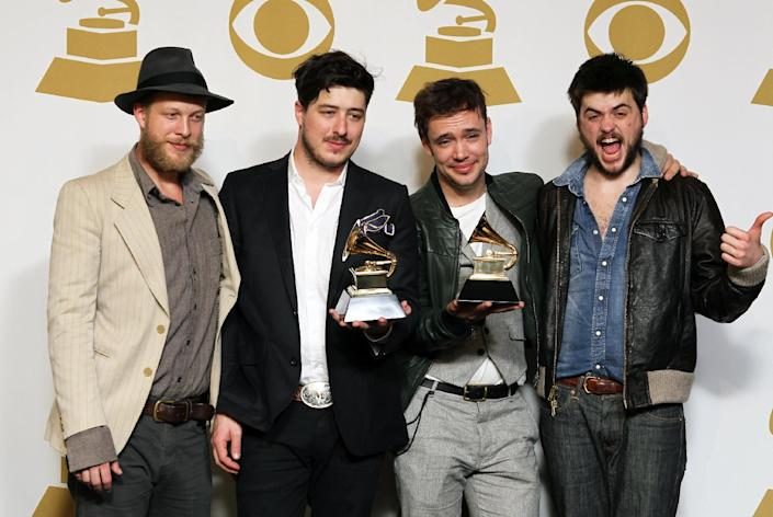 """FILE - In this Feb. 10, 2013 file photo, members of the musical group Mumford & Sons, from left, Ted Dwane, Marcus Mumford, Ben Lovett and Winston Marshall, pose backstage with the best long form music video award for """"Big Easy Express"""" and the album of the year award for """"Babel"""" at the 55th annual Grammy Awards in Los Angeles. The band on Thursday, June 13, 2013 announced it has canceled its headlining performance at Bonnaroo Music & Arts Festival in Tennessee. The decision comes after Dwane received treatment this week for a blood clot on his brain. (Photo by Matt Sayles/Invision/AP, File)"""