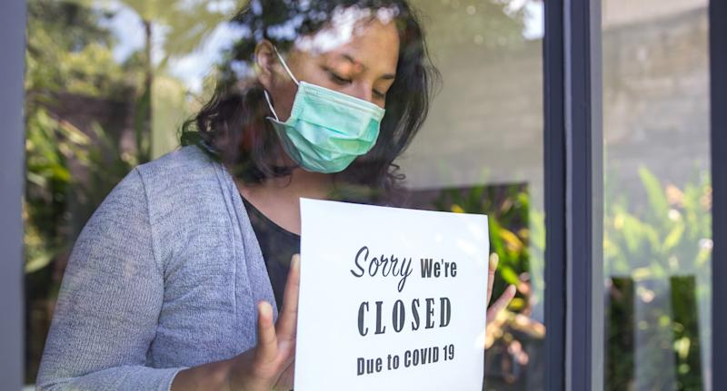 A store owner putting up a sign to close the business because of covid lockdown