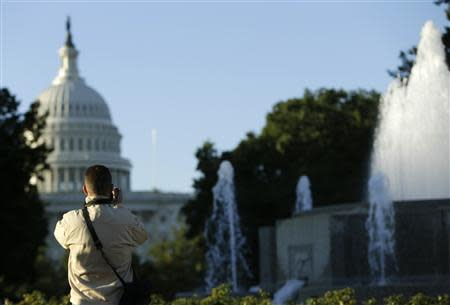 A man takes an early morning photograph of the U.S. Capitol dome in Washington