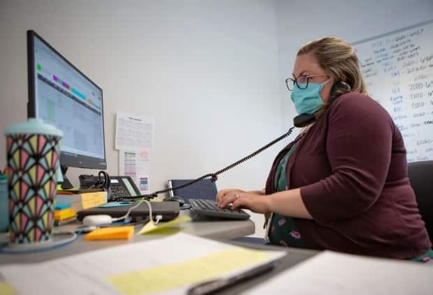 This file photo shows Heather Griggs at work as operations chief of the Umatilla County Public Health Department contact tracing centre in Pendleton, Ore. In Alberta, some contact tracing staff who had been deployed to help are being returned to their normal jobs. (Ben Lonergan/The Associated Press - image credit)