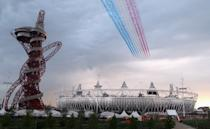 LONDON, ENGLAND - JULY 27: The Red Arrows fly over Olympic Stadium during the Opening Ceremony for the 2012 Summer Olympic Games on July 27, 2012 at Olympic Park in London, England. (Photo by Elsa/Getty Images)