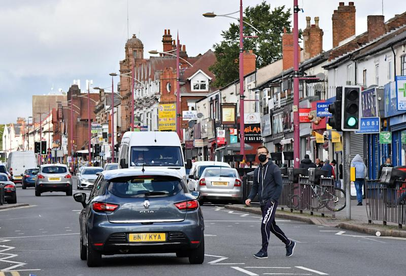 A man wearing a protective face mask crosses Soho Road in the Handsworth area of Birmingham: AFP via Getty Images