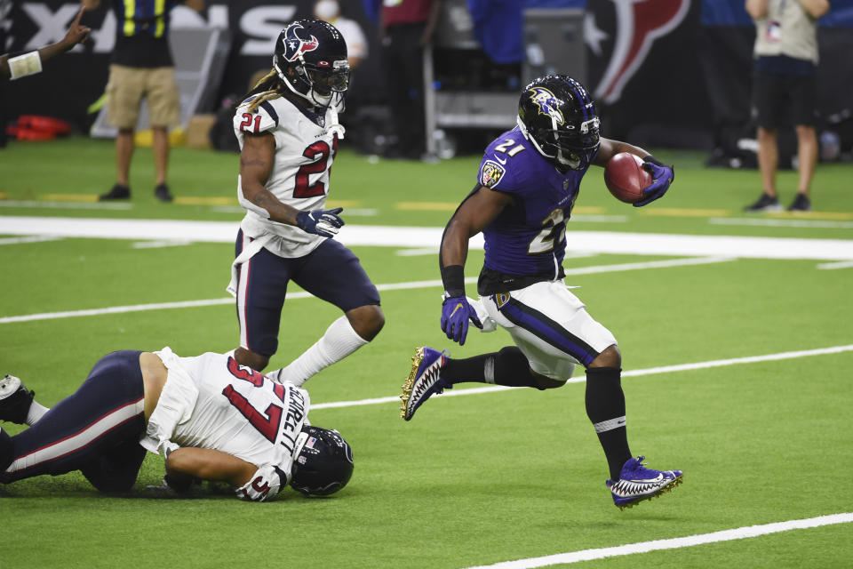 Mark Ingram runs with the ball as Texans defenders look on.