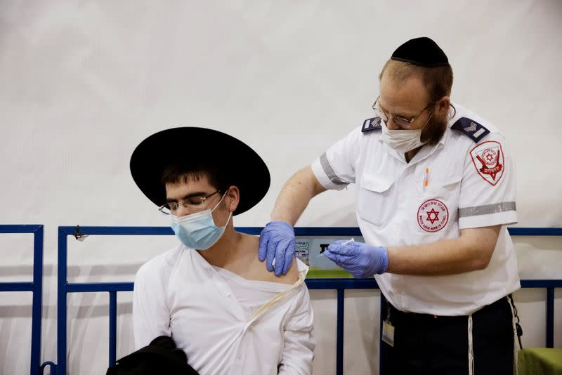 FILE PHOTO: An ultra-Orthodox Jewish man receives a vaccination against the coronavirus disease (COVID-19) at a temporary vaccination centre in the Jewish settlement of Beitar Illit, in the Israeli-occupied West Bank