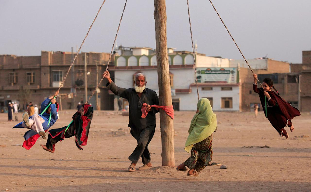 <p>A man spins children on a home made merry-go-round in a vacant lot in Peshawar, Pakistan Sept. 22, 2016. (Photo: Fayaz Aziz/Reuters) </p>