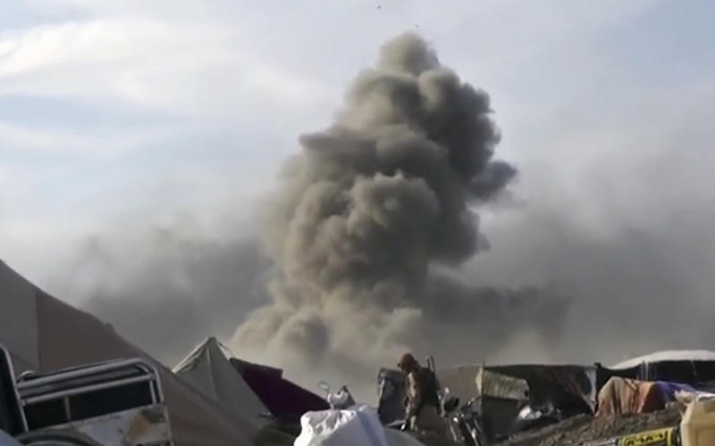 This frame grab from video posted online Monday, March 18, 2019, by the Aamaq News Agency, a media arm of the Islamic State group, shows smoke rising as an IS fighter walking inside Baghouz, the Islamic State group's last pocket of territory in Syria. U.S.-backed Syrian forces fighting the IS announced Tuesday they have taken control over an encampment in an eastern Syrian village where IS militants have been besieged for months, refusing to surrender. (Aamaq News Agency via AP)