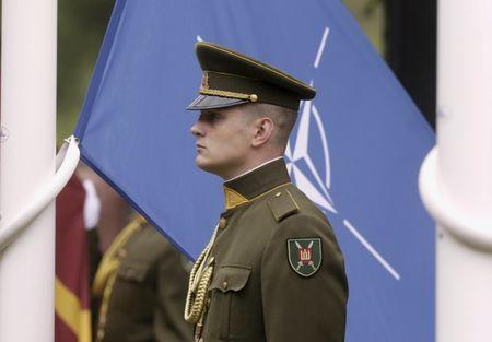 A Lithuanian army soldier stands near the NATO flag during the NATO Force Integration Unit inauguration event in Vilnius, Lithuania, September 3, 2015. REUTERS/Ints Kalnins/File Photo