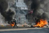 An Iraqi protester walks past burning tyres during clashes with police during anti-government demonstrations in the city of Nasiriyah in January