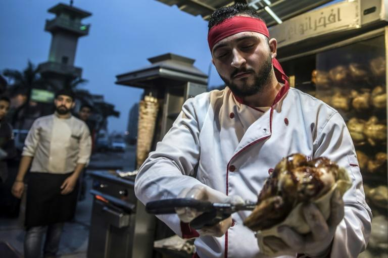 Syrian refugee Adel Bezmawy, co-founder of the sports academy in Egypt's Alexandria, Syrian Talented Academy, works at a restaurant in the coastal city on January 4, 2018