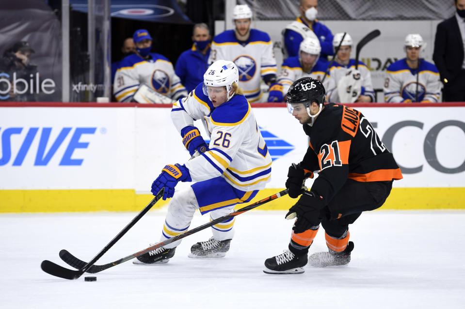 Buffalo Sabres' Rasmus Dahlin, left, plays the puck ahead of Philadelphia Flyers' Scott Laughton during the first period of an NHL hockey game, Sunday, April 11, 2021, in Philadelphia. (AP Photo/Derik Hamilton)