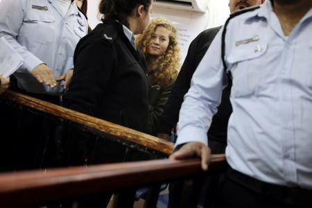 Palestinian teen Ahed Tamimi enters a military courtroom escorted by Israeli security personnel at Ofer Prison, near the West Bank city of Ramallah, February 13, 2018. REUTERS/Ammar Awad/Files