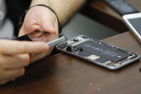 A worker checks an iPhone in a repair store in New York