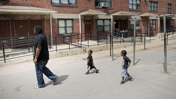PHOTO: A man walks through the courtyard outside his apartment in the Gilmor Homes with two of his six children, one year after Freddie Gray died, April 19, 2016, in Baltimore. (Chip Somodevilla/Getty Images, FILE)