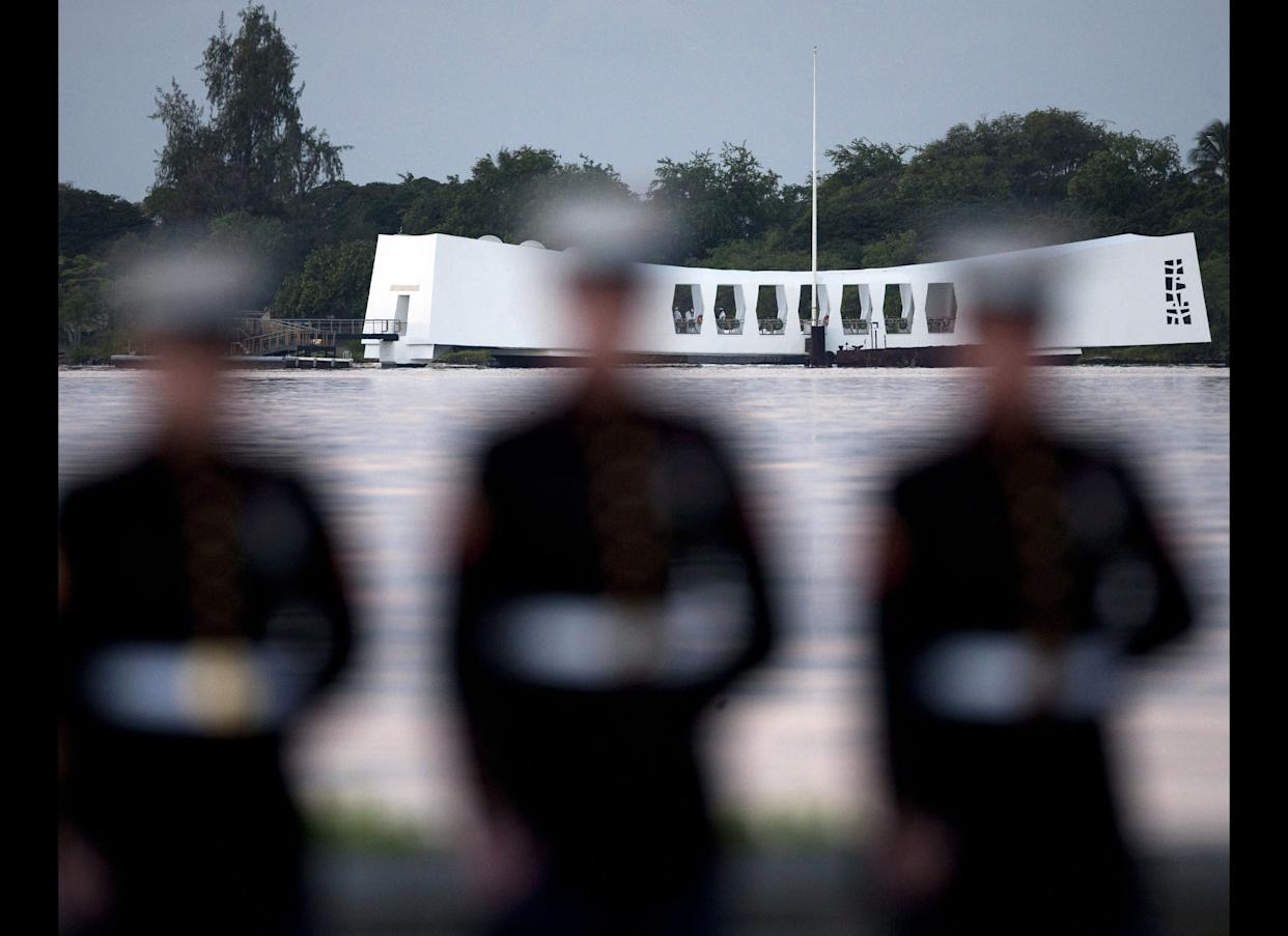 With the USS Arizona memorial in the background, Marines stand at attention early Tuesday.