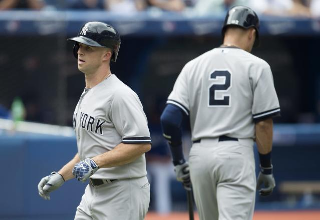 New York Yankees' Brett Gardner, left, runs past teammate Derek Jeter following his leadoff home run in the first inning of a baseball game against the Toronto Blue Jays in Toronto, Sunday, Aug. 31, 2014. (AP Photo/The Canadian Press, Darren Calabrese)