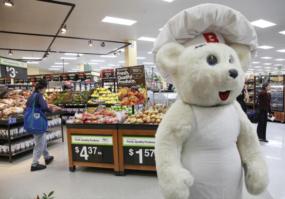 Bimbo Bakeries USA's  Bimbo Bear, right, welcomes consumers at the new Walmart Neighborhood Market, opening its 34,000 square foot store in the Chinatown district  of Los Angeles Thursday, Sept. 19, 2013. (AP Photo/Nick Ut)