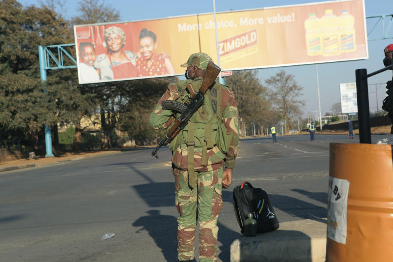 An armed soldier stands on a deserted street in Harare, Friday, July, 31, 2020. Zimbabwe's capital, Harare, was deserted Friday, as security agents vigorously enforced the country's lockdown amidst planned protests. Police and soldiers manned checkpoints and ordered people seeking to get into the city for work and other chores to return home. (AP Photo/Tsvangirayi Mukwazhi)