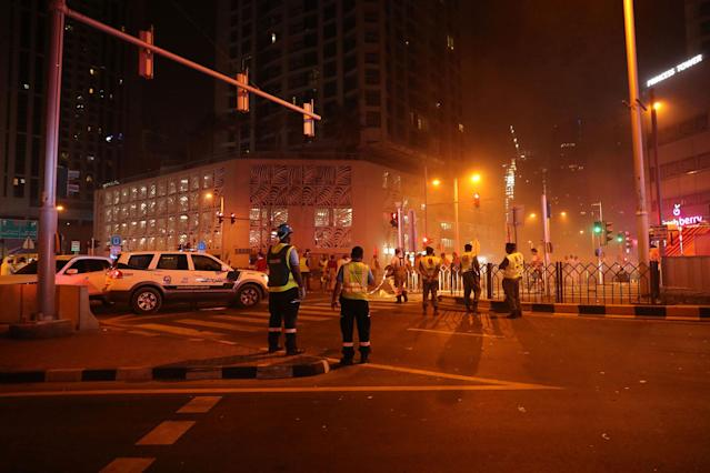 <p>Firefighters stand outside the burning 1,105 foot tall Torch tower skyscraper on August 4, 2017 in Dubai. (Photo: Karim Sahib/AFP/Getty Images) </p>