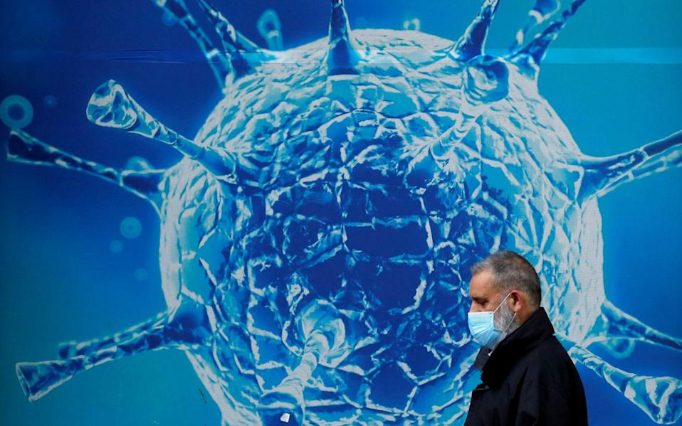 A man wearing a protective face mask walks past an illustration of a virus outside a regional science centre - Phil Noble/REUTERS