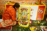 A Bharatiya Janata Party (BJP) activist performs Hindu rituals in front of a picture of the deity Ram inside a BJP office in Kolkata on August 5, 2020, to mark the groundbreaking ceremony of the Ram Temple in Ayodhaya. - India's Prime Minister Narendra Modi will lay the foundation stone for a grand Hindu temple in a highly anticipated ceremony on August 5 at a holy site that was bitterly contested by Muslims, officials said. The Supreme Court ruled in November 2019 that a temple could be built in Ayodhya, where Hindu zealots demolished a 460-year-old mosque in 1992. (Photo by Dibyangshu SARKAR / AFP) (Photo by DIBYANGSHU SARKAR/AFP via Getty Images)