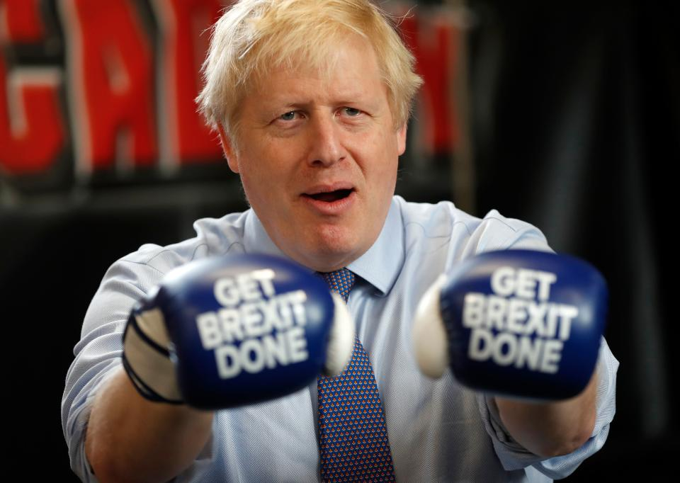 """Britain's Prime Minister and leader of the Conservative Party, Boris Johnson wears boxing gloves emblazoned with """"Get Brexit Done"""" as he poses for a photograph at Jimmy Egan's Boxing Academy in Manchester north-west England on November 19, 2019, during a general election campaign trip. - Britain will go to the polls on December 12, 2019 to vote in a pre-Christmas general election. (Photo by Frank Augstein / POOL / AFP) (Photo by FRANK AUGSTEIN/POOL/AFP via Getty Images)"""