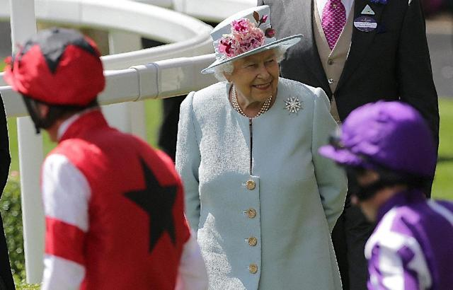 Britain's Queen Elizabeth II (C) reacts as jockeys and horses parade in the ring on the second day of the Royal Ascot horse racing meet, in Ascot, west of London, on June 20, 2018. The five-day meeting is one of the highlights of the horse racing calendar. Horse racing has been held at the famous Berkshire course since 1711 and tradition is a hallmark of the meeting. Top hats and tails remain compulsory in parts of the course while a daily procession of horse-drawn carriages brings the Queen to the course. (AFP Photo/Daniel LEAL-OLIVAS)
