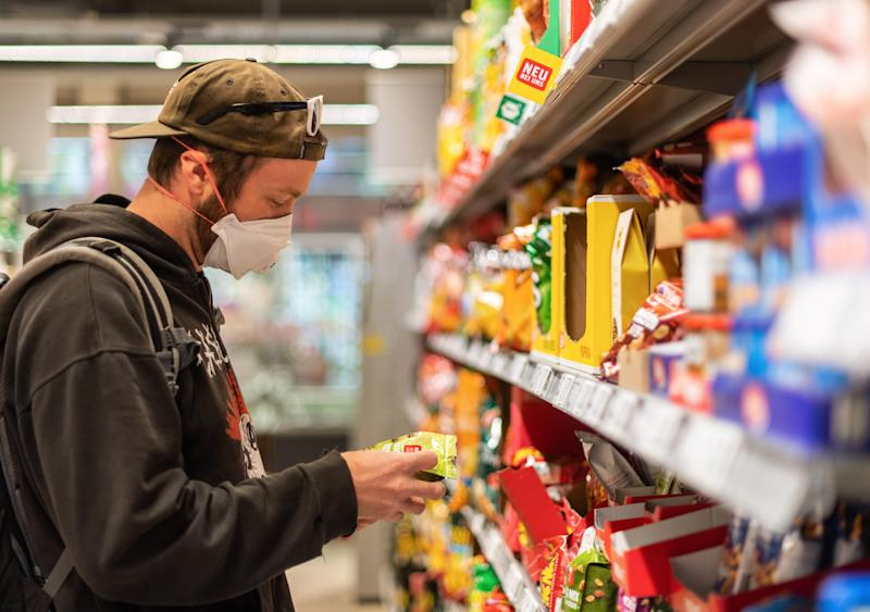 20 April 2020, Saxony, Dresden: A customer stands in front of a shelf in a supermarket, wearing a mouthguard. Today, Monday, the first corona pads will be gradually loosened, but in Saxony, the retail trade is obliged to wear masks. Photo: Robert Michael/dpa-Zentralbild/dpa (Photo by Robert Michael/picture alliance via Getty Images)