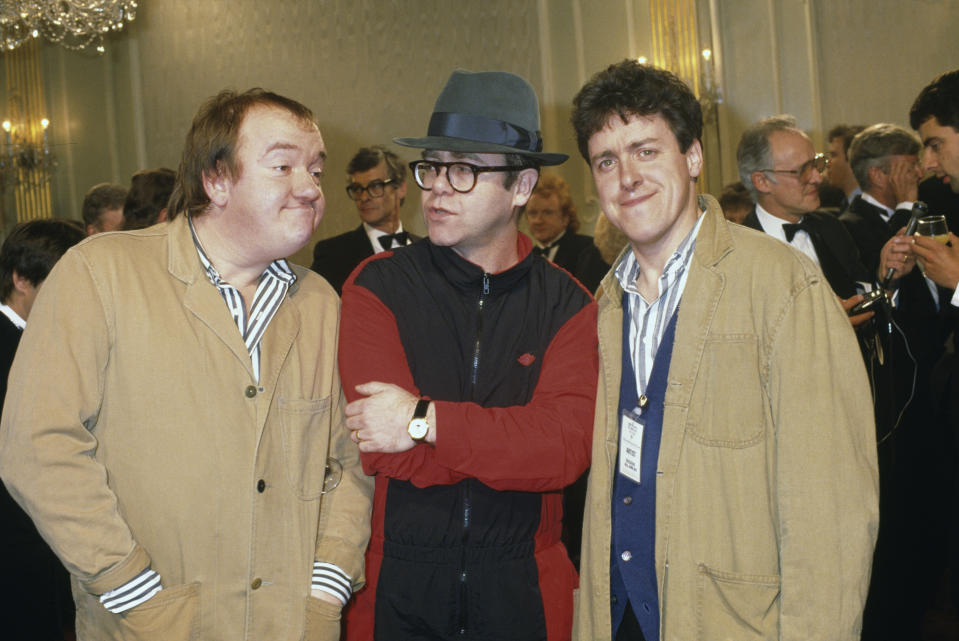 British comedians Mel Smith (left) and Griff Rhys Jones (right), stars of the new TV comedy series 'The World According To Smith and Jones', with singer Elton John at the London Palladium, 4th December 1987. (Photo by Fox Photos/Hulton Archive/Getty Images)