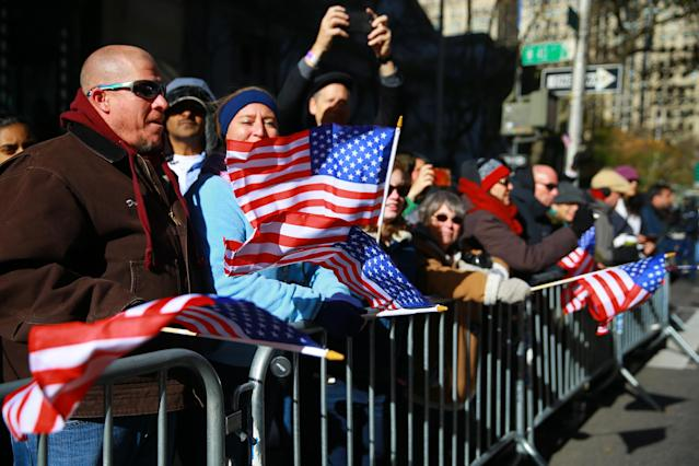<p>Spectators wave flags as members of the armed forces march during the Veterans Day parade on Fifth Avenue in New York on Nov. 11, 2017. (Photo: Gordon Donovan/Yahoo News) </p>