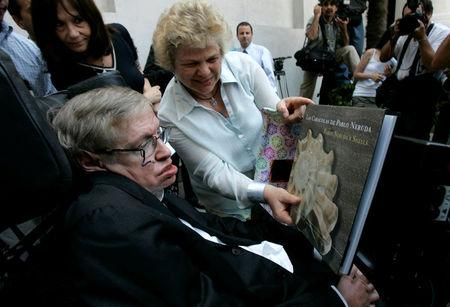 FILE PHOTO: British physicist Stephen Hawking looks at a book of Chile's Nobel Laureate Pablo Neruda after a meeting with Chile's President Michelle Bachelet (unseen) at the Presidential Palace in Santiago January 17, 2008.  REUTERS/Victor Ruiz Caballero/File Photo