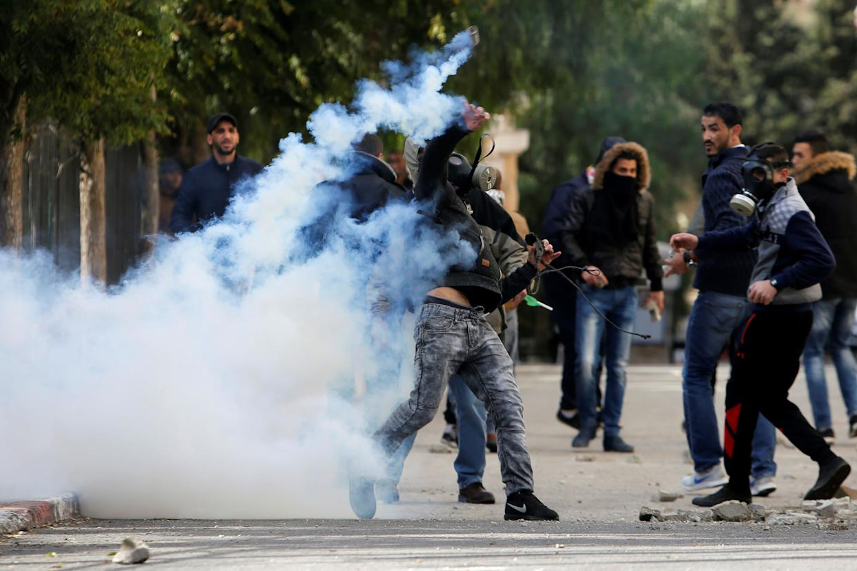 A Palestinian protester hurls back a tear gas canister fired by Israeli troops in the West Bank city of Bethlehem December 7, 2017.